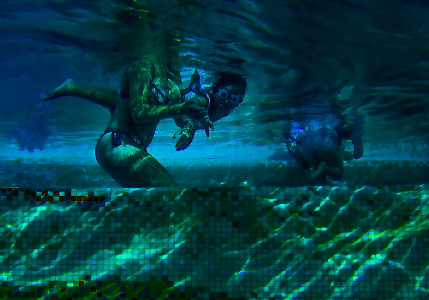 A little girl swims and floats underwater wearing goggles - Blue and Green - Underwater photography
