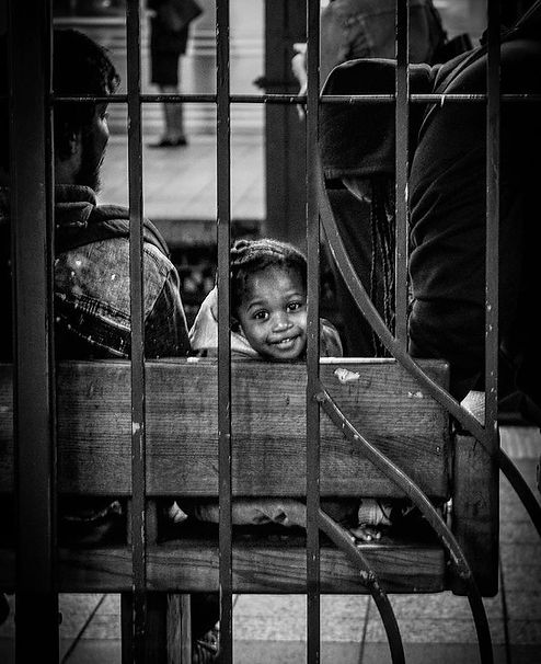 Child peeks through bars and smiles on bench - Underground in NYC subway - Street photography