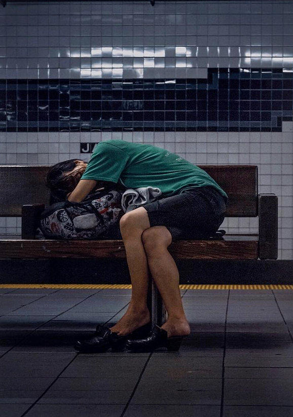 Woman asleep on a bench underground in NYC subway station - Street photography