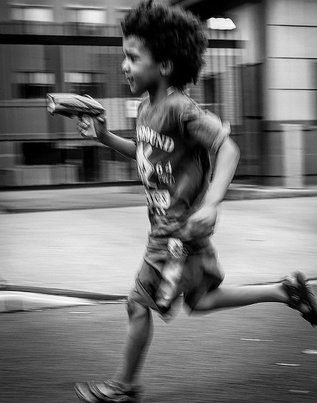 Young boy running in Brooklyn, NY street with toy gun - Black and white photography