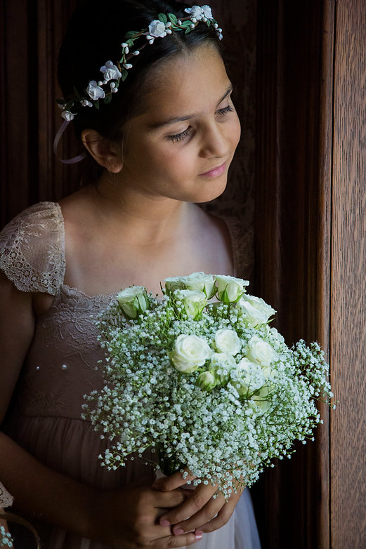 Brides maid looking out window at wedding - Wedding photograph