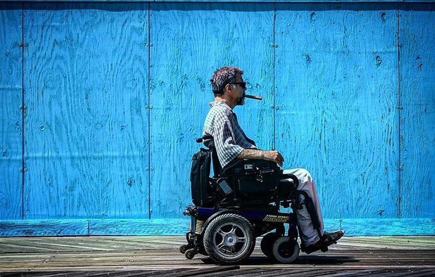 Man in wheelchair against Blue wood wall - NYC - Coney Island - Street photography