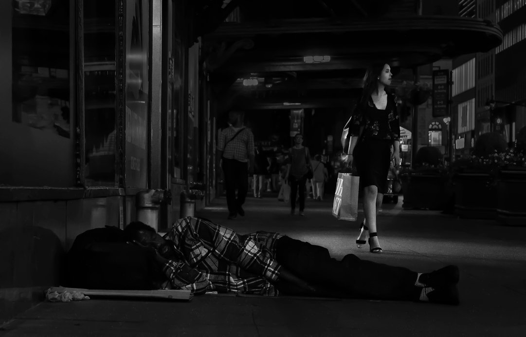 Homeless man sleeping in the street with a woman and her shopping bags - Black and white photography