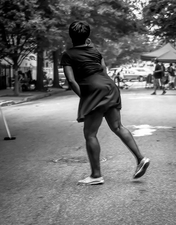 Woman dancing in street at block party in Brooklyn, NY - Black and white photography
