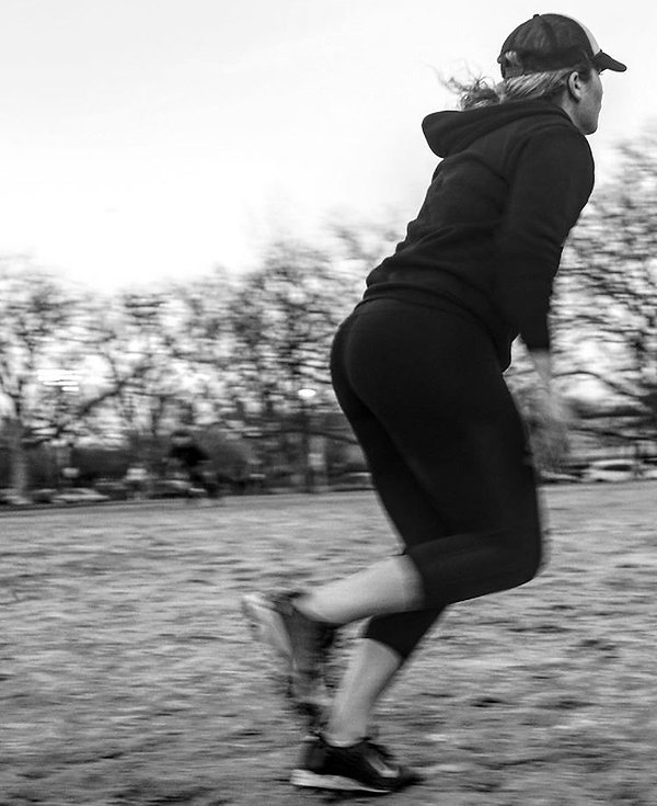 Woman running on sports field - NYC - Street photography - Black and white photography