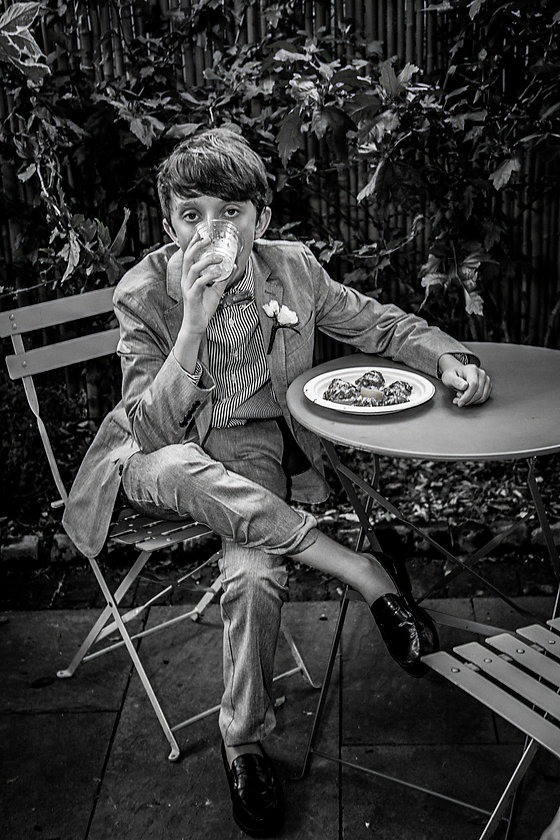 Young boy sitting at wedding table eating  - Wedding photography - Black and white photography