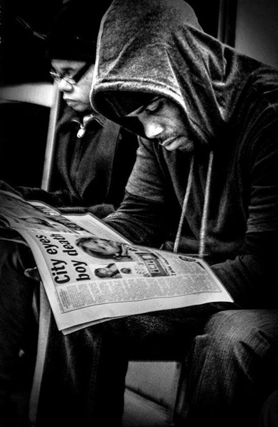 Young man reads newspaper in NYC subway - Black and white photography