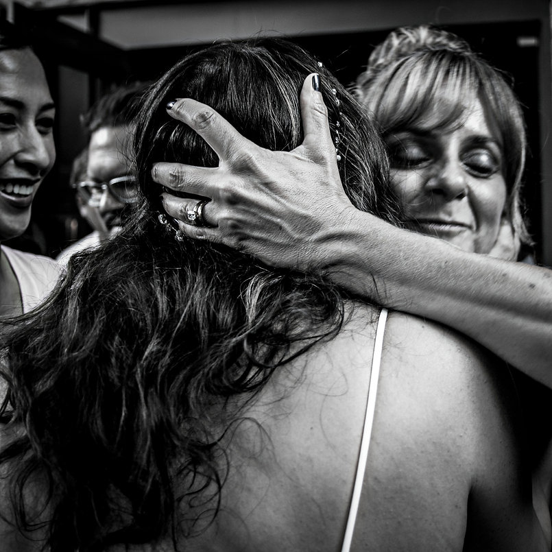 Bride being hugged at wedding party  - Wedding photography - Black and white photography