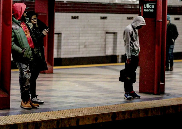 People standing on a subway station platform in NYC - Man looks down onto tracks thinking - Street photography