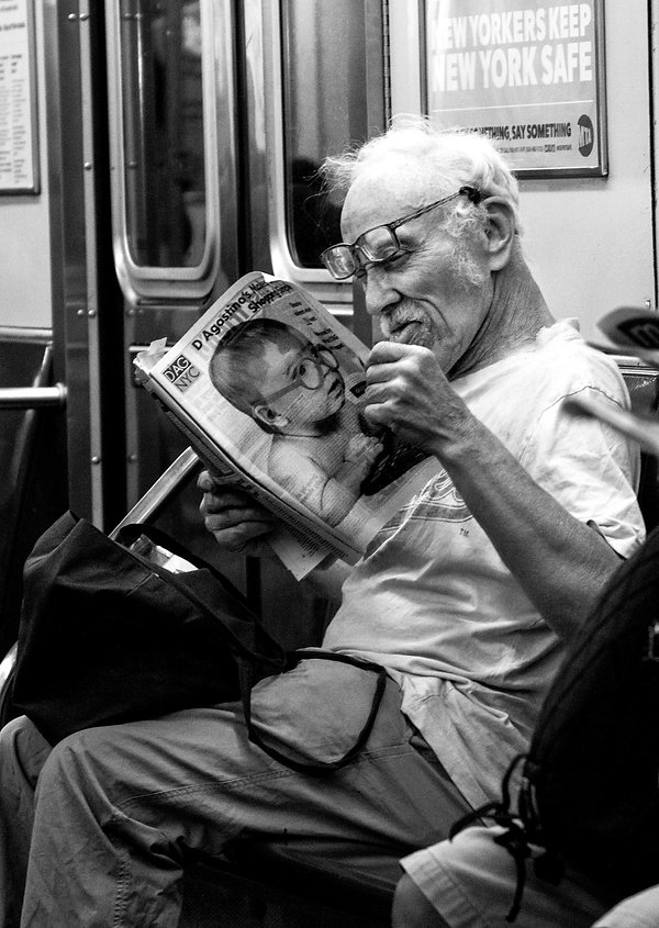 Old man reads newspaper wearing glasses - Front page of newspapeer has baby with glasses - NYC - Street photography