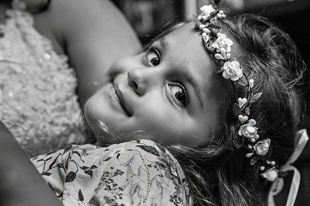 Young girl smiling in the arms of a bride at wedding  - Wedding photography - Black and white photography