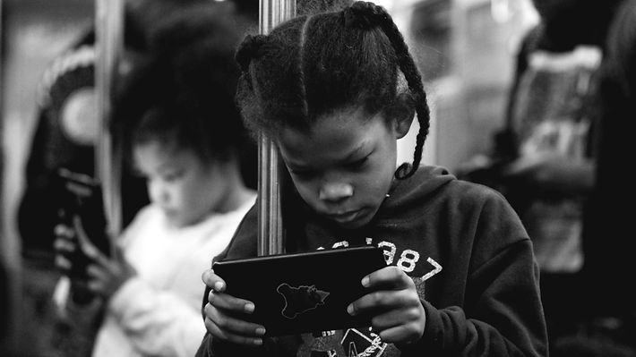 Child looks at I pad on NYC subway - Street photography