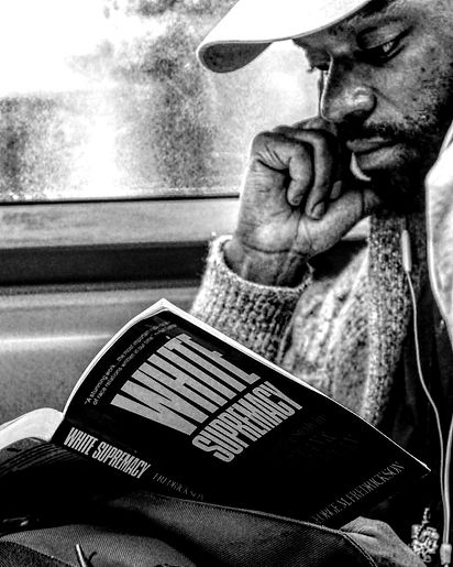 Man reads book titles White supremacy on Subway in NYC - Black and white photography