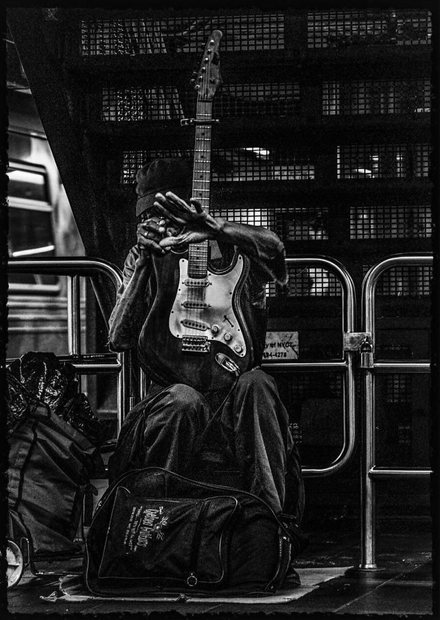 Street musician hiding from camera on NYC su bway platform - Black and white street photography