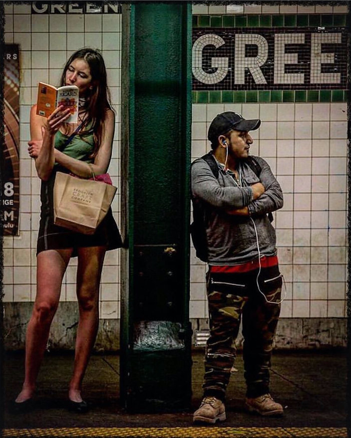 Tall woman stands reading a book beside man on subway platform - NYC - Street photography