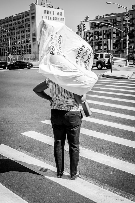 Woman carrying party city bag of ballons in street Brooklyn, NY - Black and white photography