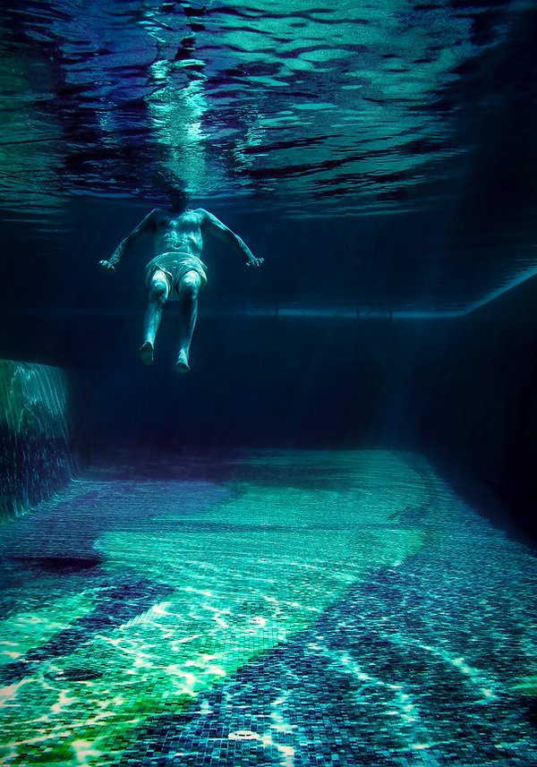 A man floats underwater - blue and green - Underwater photography