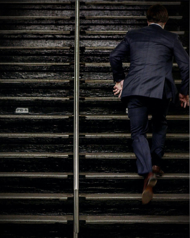Man in suit runs up steps in a NYC subway - Street photography