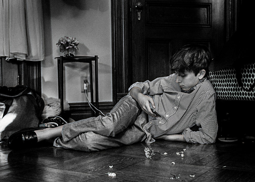 Boy laying on ground playing with his phone - Wedding photography - Black and white photography