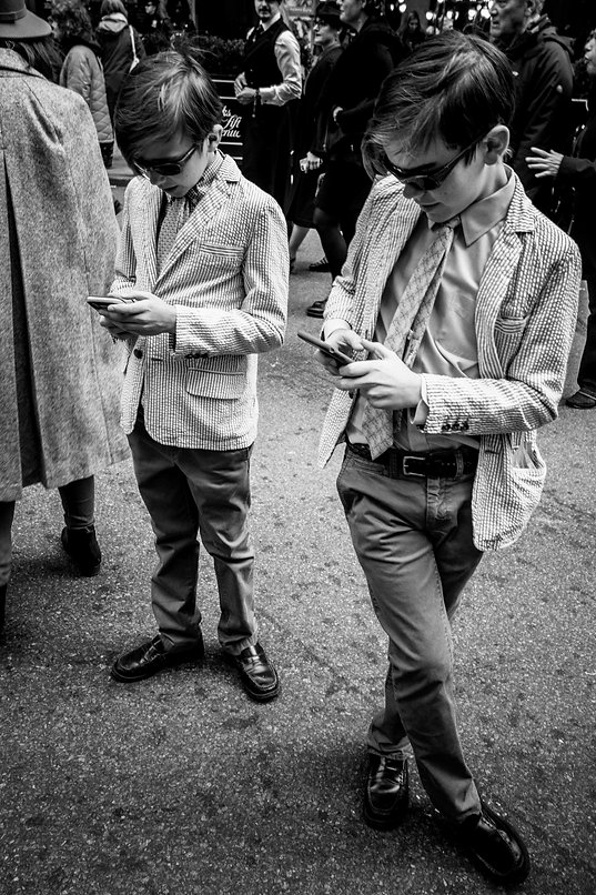 Two young boys on cell phones in matching putfits - NYC - street photography - Black and white photography.
