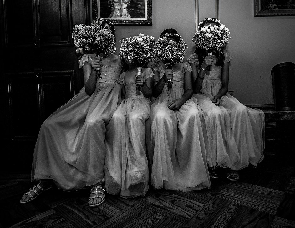 Young brides maids covering face with flowers at wedding party  - Wedding photography - Black and white photography