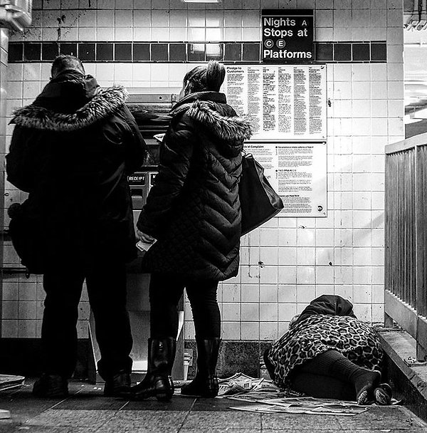 Couple buying subway ticket next to a sleeping homeless woman - Black and white street photography