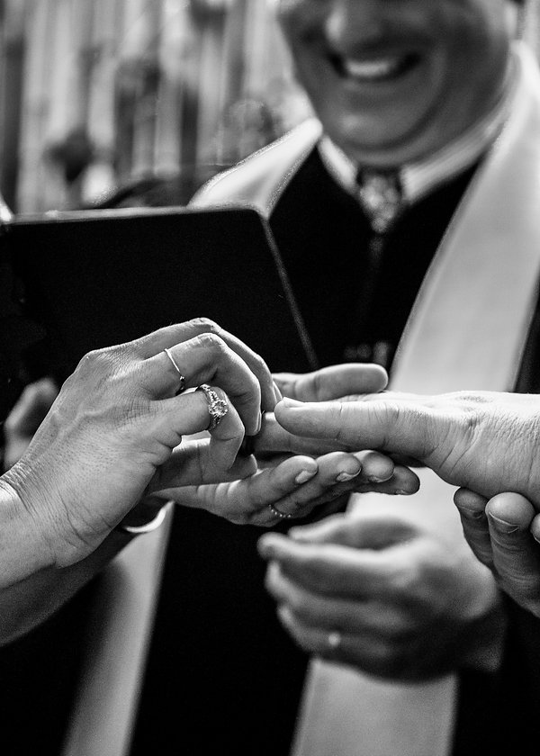 Bride putting wedding band on grooms finger - Wedding photography - Black and white photography