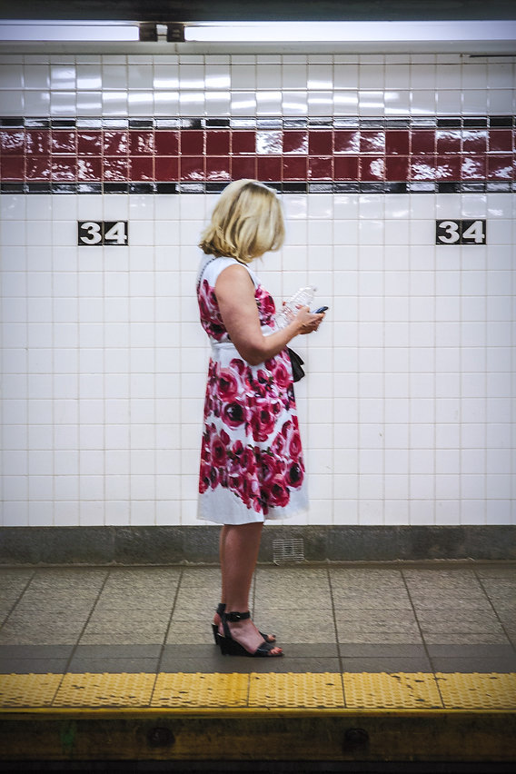 Woman in floral dress looks at her phoone on a subway platform in NYC - Street photography