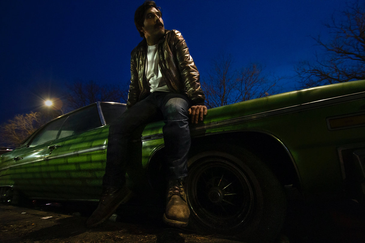 Man sits on vintage car - Brooklyn NYC - Mustache model
