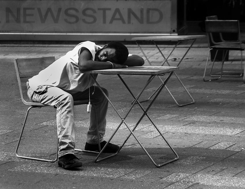 Man sleeeping on table - New York - Black and White photography - Street photography