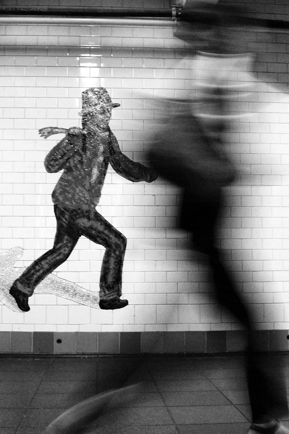 Open shutter - Woman walks past tiled wall in underground passage to subway in NYC - Black and white photography
