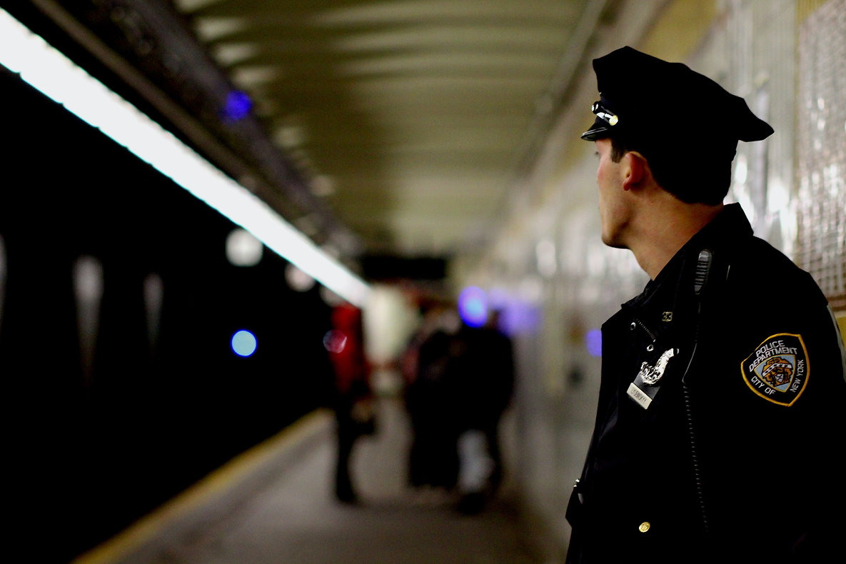 NYC police officer looks at kids talking on a subway platform - Street photography