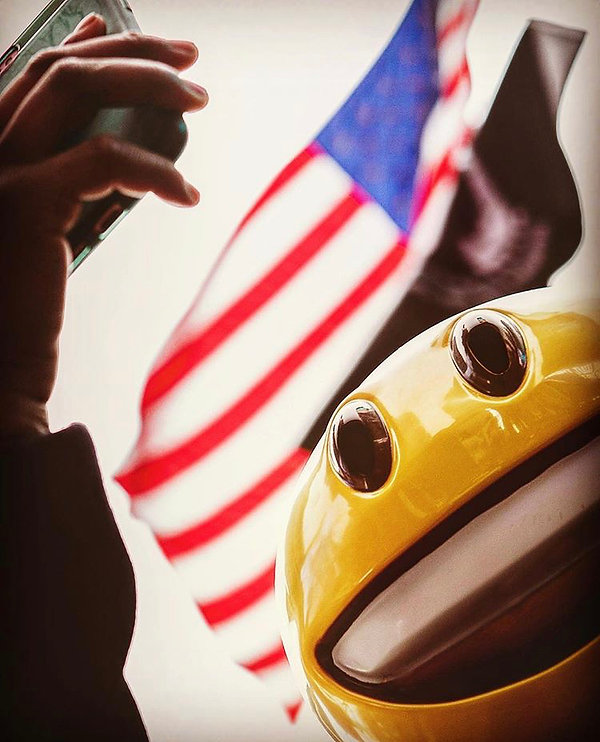 Smiley emoji looking at phone - American flag - Street photography