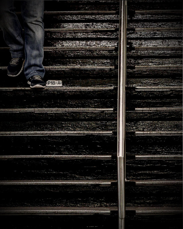 Man walks down steps to subway platform wearing jeans and sneakers - Street photography
