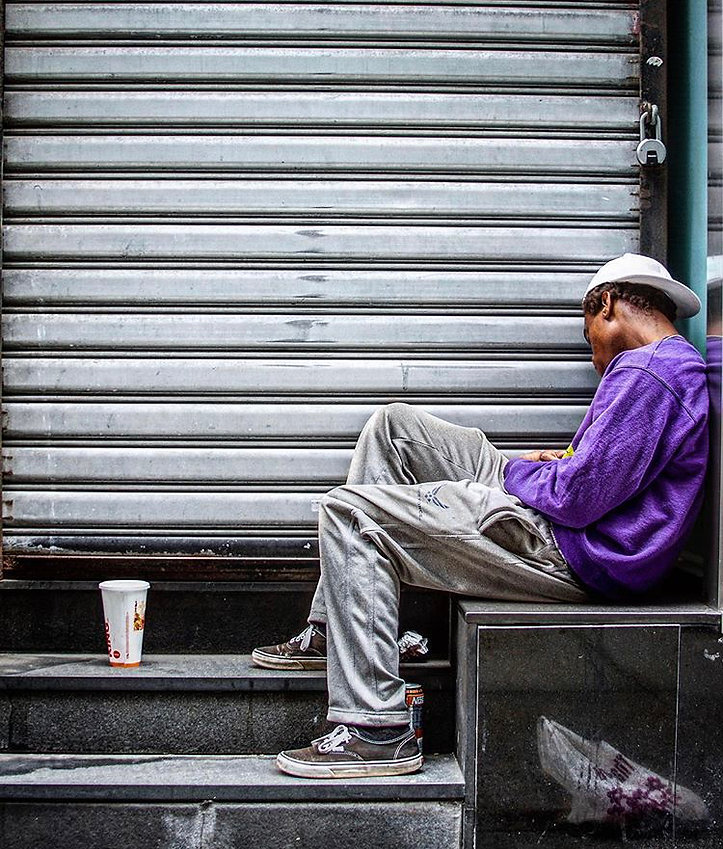 Man sleeping against roll gate - NYC - Purple - Street photography