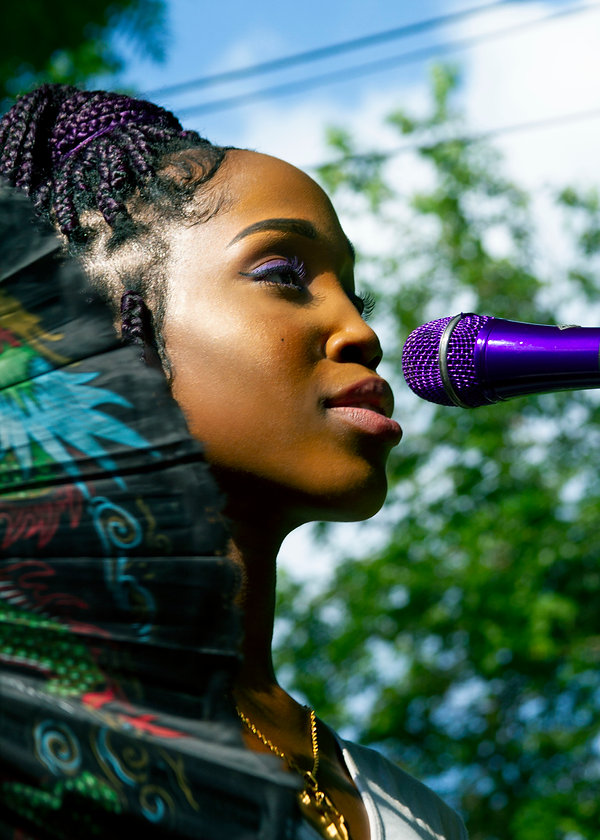 Singer with purple braids at a backyard music festival in Brooklyn NY
