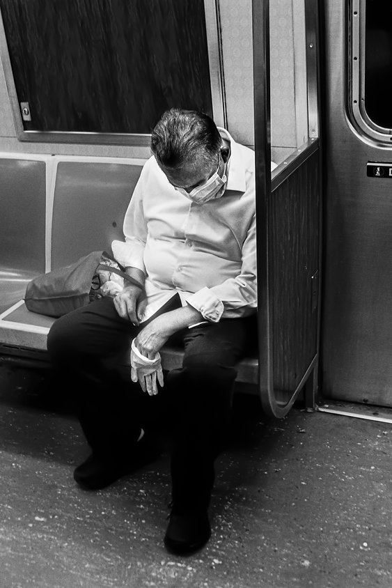 Man asleep wearing mask and holding a glove on NYC train - Black and white street photography