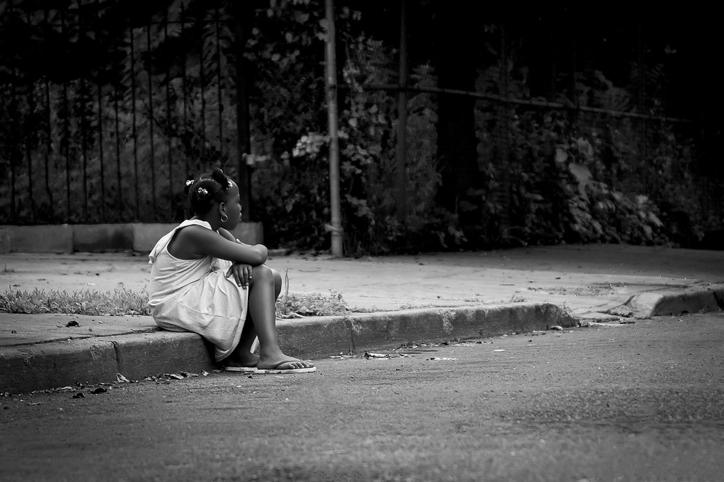 Young girl sitting on curb alone   - Black and white photography