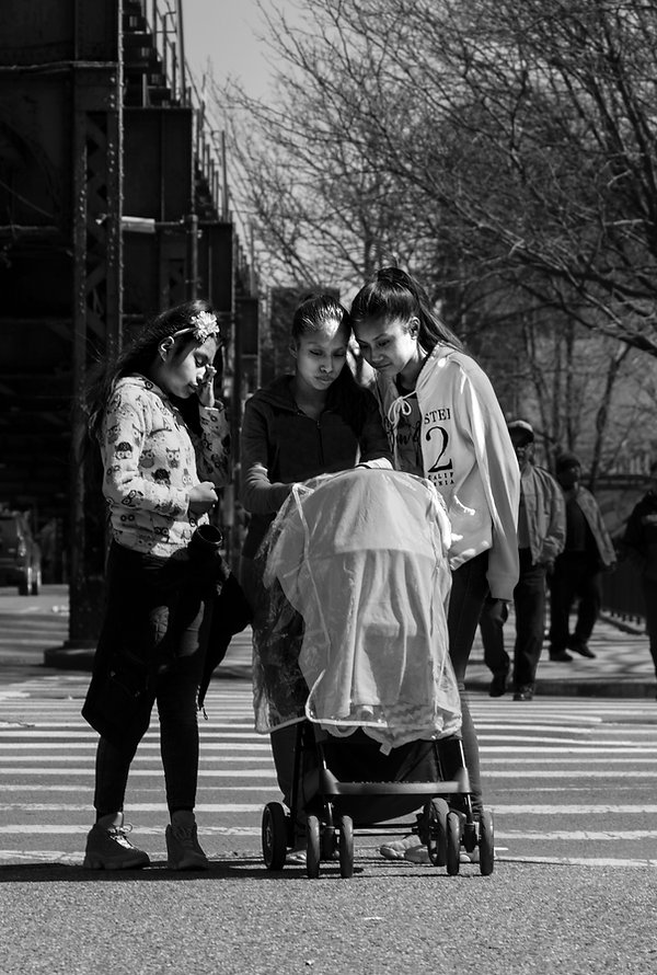 Yong HIspanic girls looking at baby in street - Black and white photography