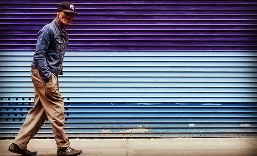 Man walking in front of purple and blue roll gate - Street photography