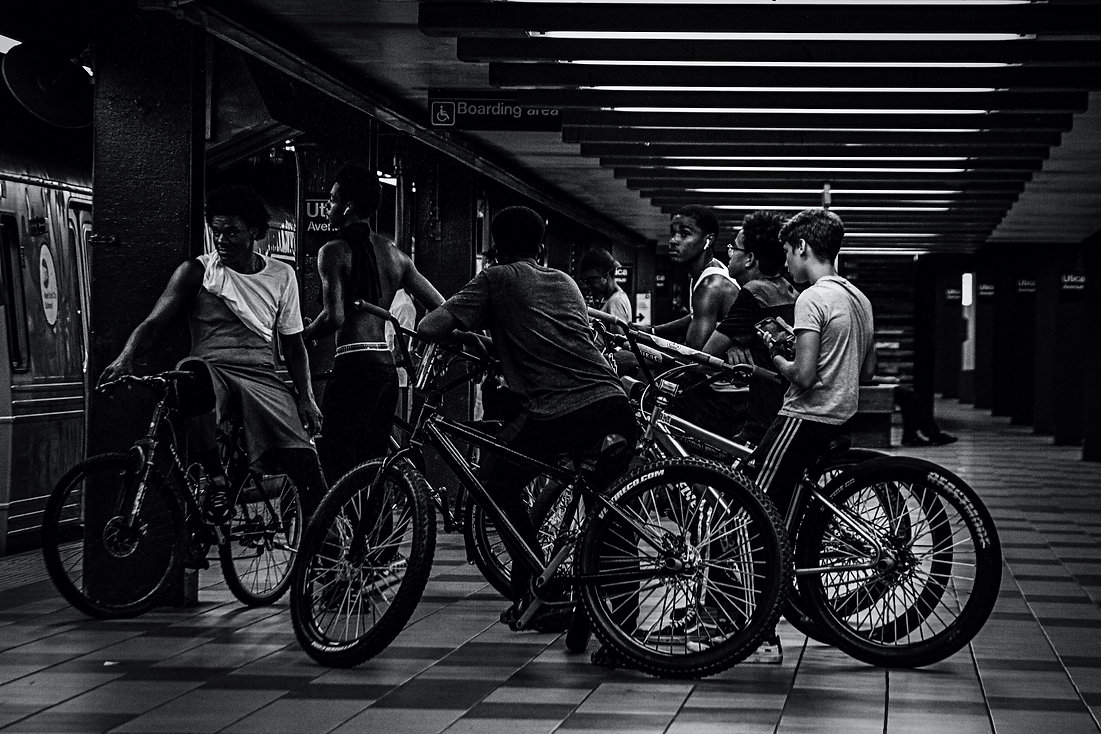 Group of kids sitting on bikes waiting for a train on a NYC su bway platform. - Black and white street photography