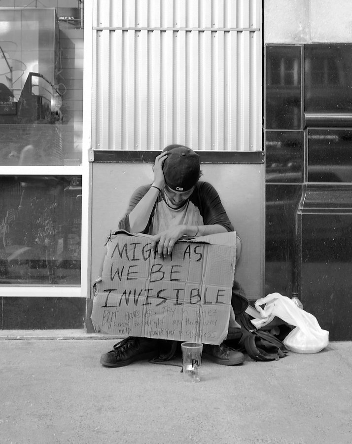 Homeless man holds sign saying might as well be invisible in NYC - Black and white street photography