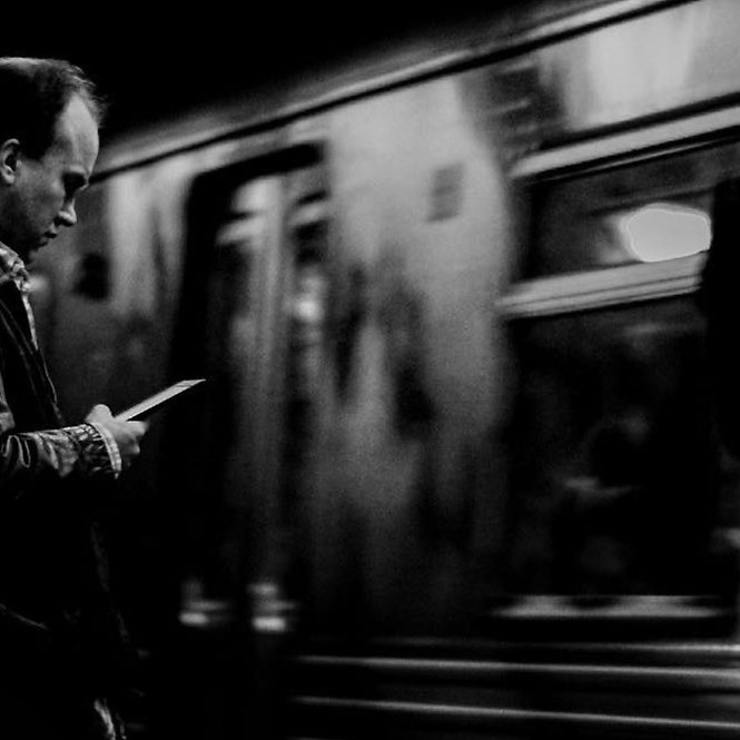 Man. checking his phone on a subway platform - NYC - Black and white photography
