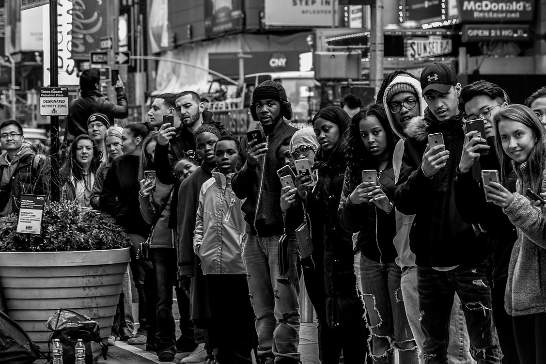 Group of people with cell phones in NYC watching street performance - Black and white street photography