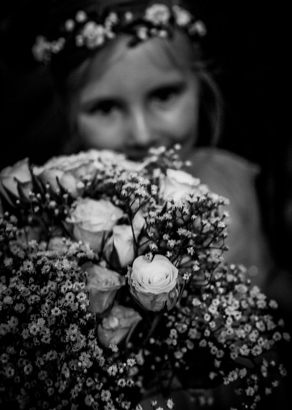 Flower girl holding flowers to camera at wedding - Black and white photography - Wedding photography