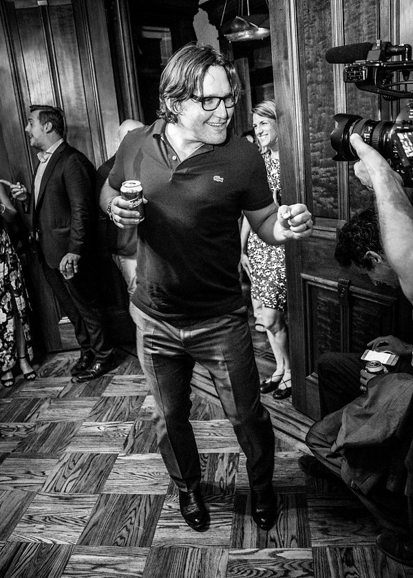 Groom dancing to a camera at wedding party  - Wedding photography - Black and white photography