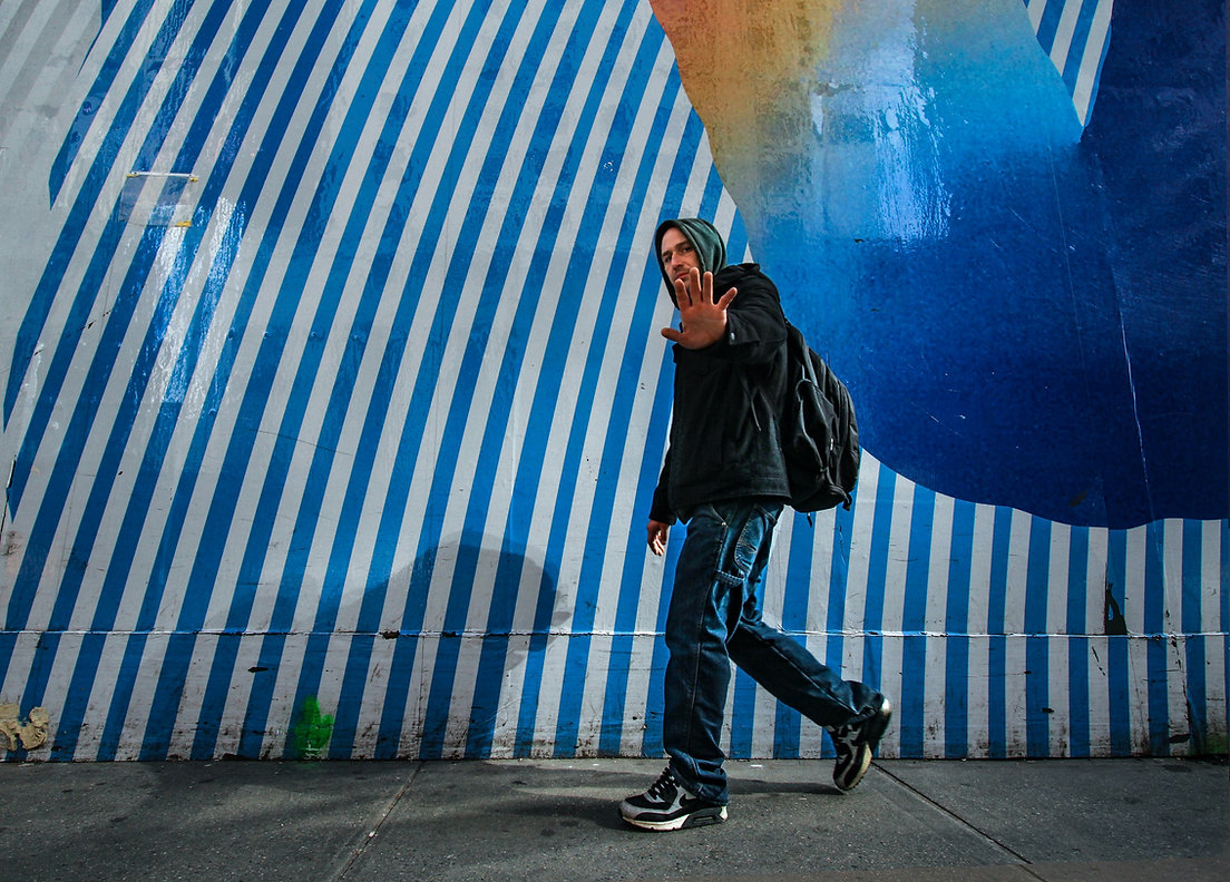 Man walking against blue and white striped wall - NYC - street photography