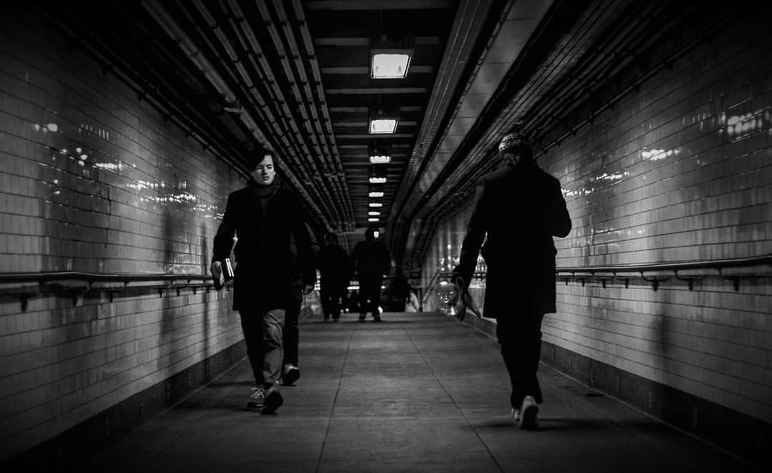 Two men pass each other in an underground subway passage way - Black and white photography