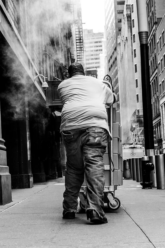Man pushing boxes in steam - NY - - Black and white photography