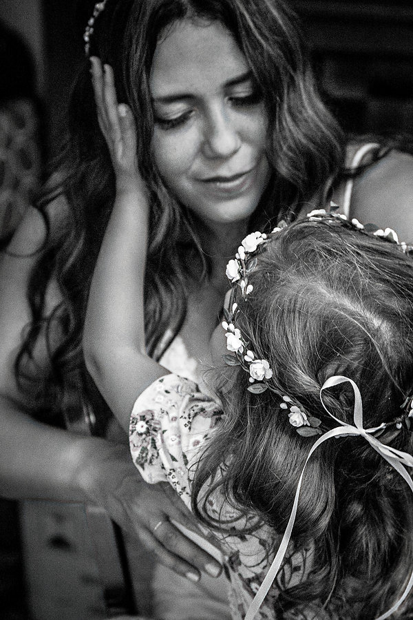 Flower girl holding brides face at wedding  - Wedding photography - Black and white photography